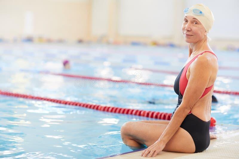 Smiling Senior Woman Sitting by Pool stock image
