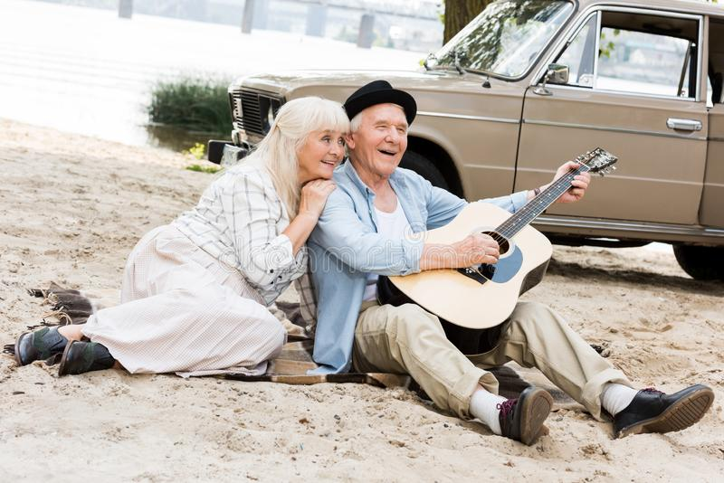 Smiling senior woman sitting on sand with man playing guitar against beige. Car royalty free stock images