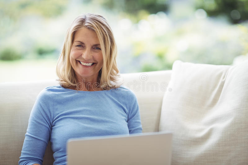 Smiling senior woman sitting on sofa with laptop in living room royalty free stock images