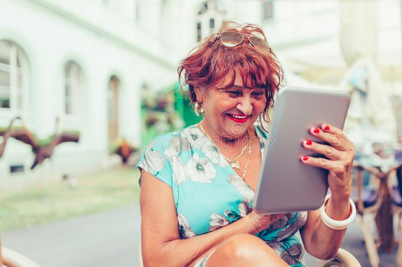 Smiling senior woman spending time in a outdoor cafe using digital tablet royalty free stock images