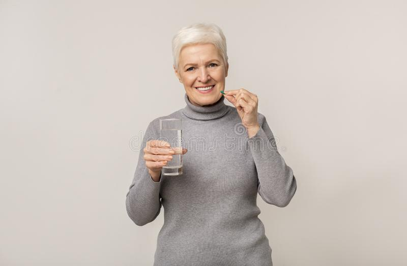 Smiling senior woman taking pills and holding glass of water royalty free stock photography
