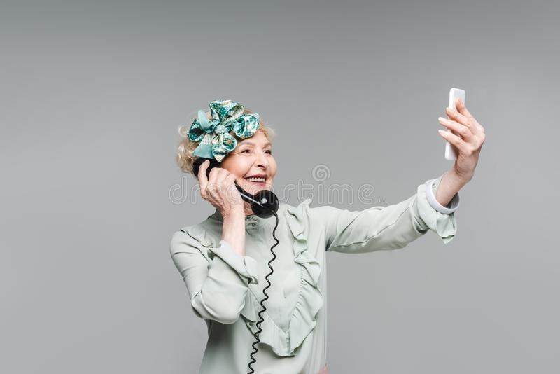 Smiling senior woman taking selfie while talking by vintage phone. Isolated on grey royalty free stock images