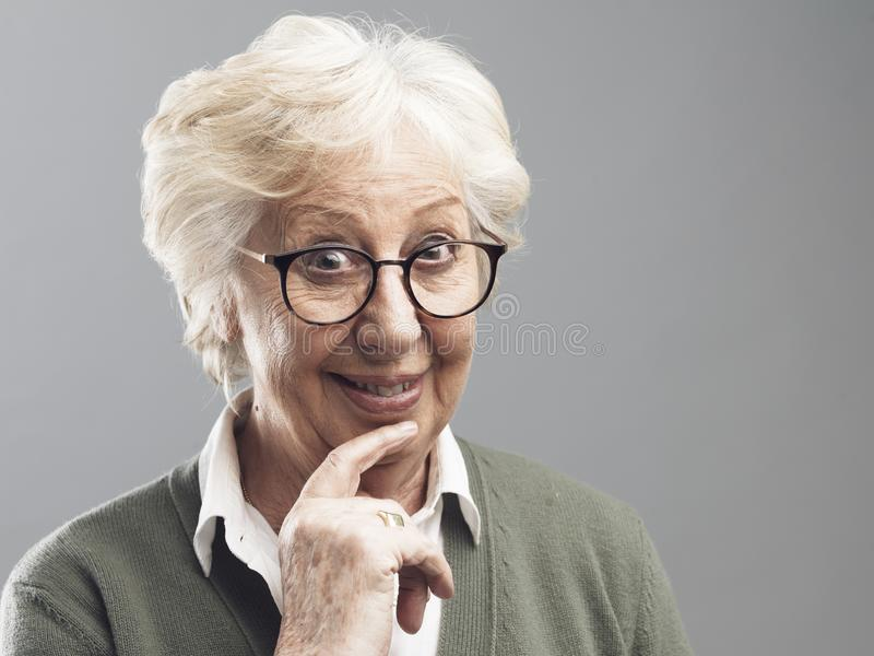 Smiling senior woman thinking with hand on chin. Opportunity and solutions concept stock image