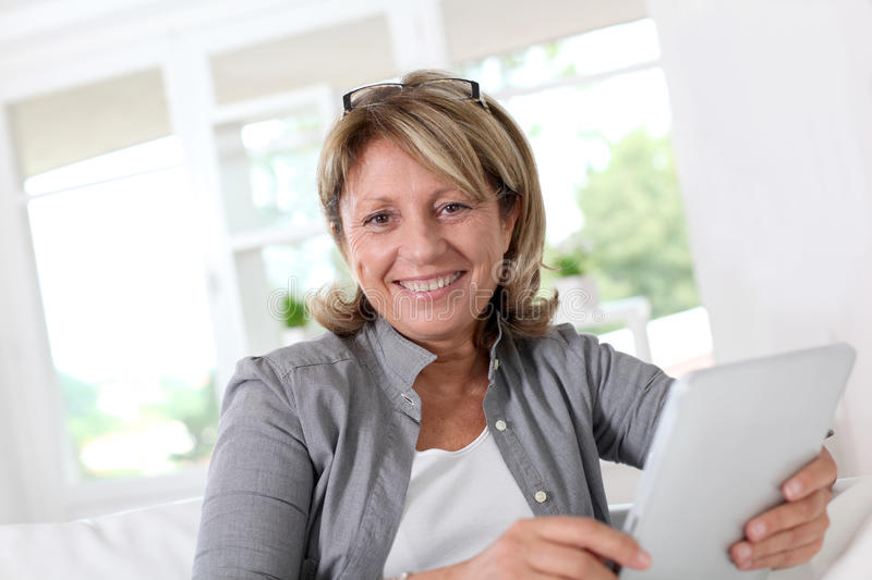 Smiling senior woman using tablet at home stock images