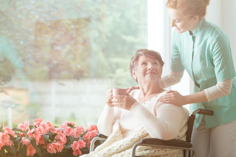 Smiling senior woman in wheelchair. Caregiver in uniform standing behind a smiling senior women in a wheelchair drinking tea in a nursing house royalty free stock photos