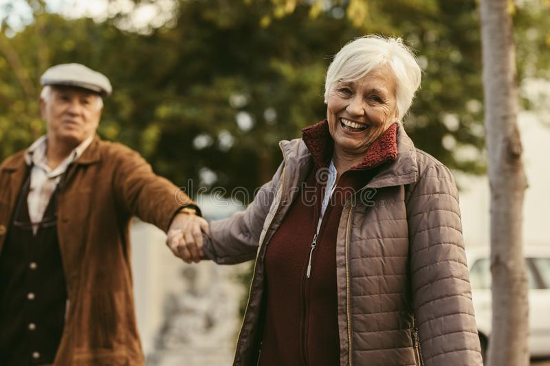 Happy senior couple walking outdoors on a winter day. Smiling senior women holding hand of her partner and walking in front outdoors. Happy senior couple walking stock photography