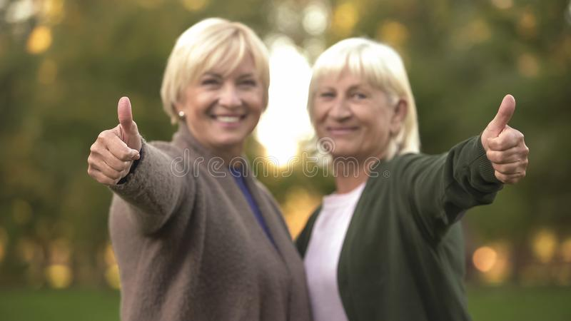 Smiling senior women showing thumbs up gesture, hugging and resting at park royalty free stock images