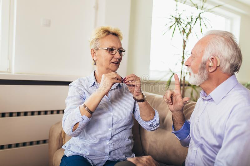 Senior woman talking using sign language with her hearing impairment man stock images
