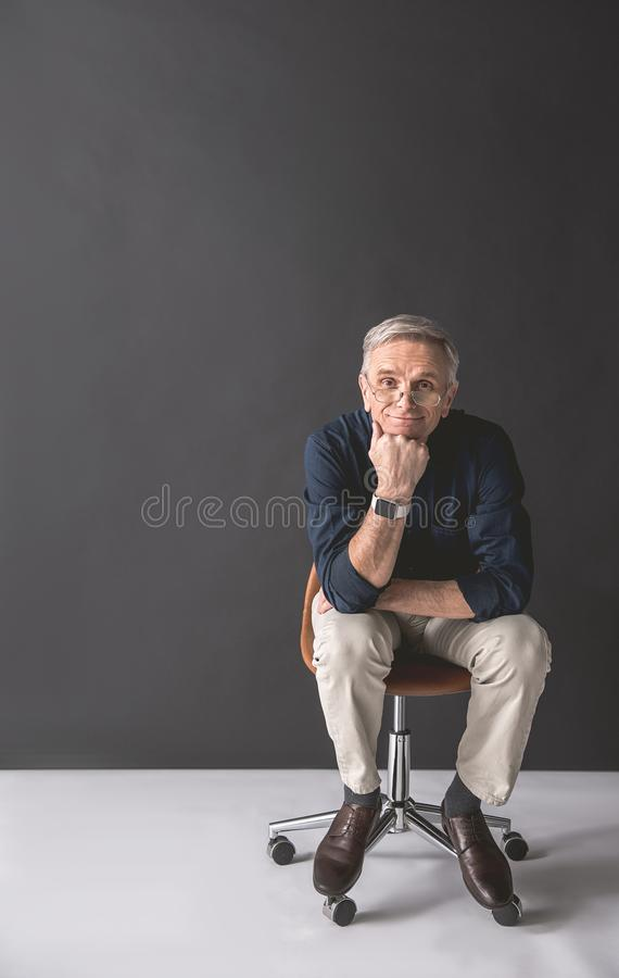 Smiling senior worker locating on chair stock photos