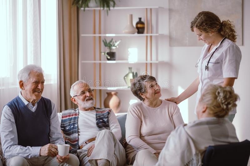 Seniors talking with nurse in the retirement home. Smiling seniors talking with nurse in the retirement home royalty free stock photo