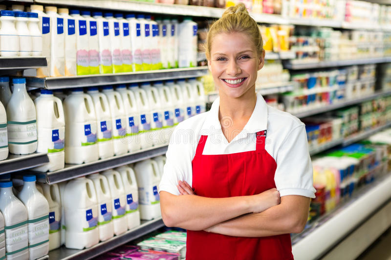 Smiling shop assistant with arms crossed stock images