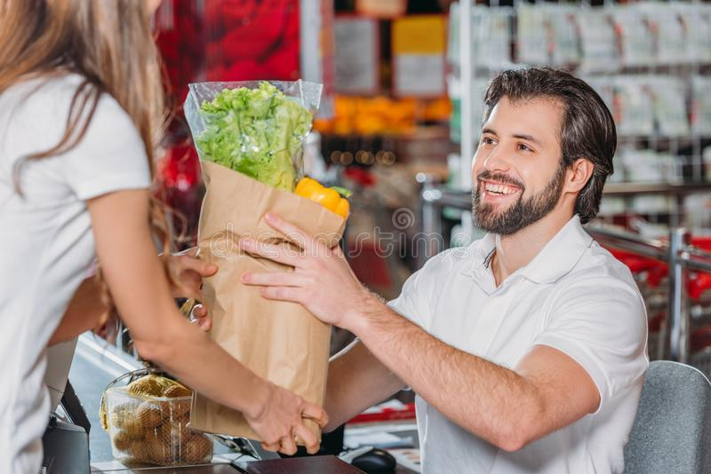smiling shop assistant giving purchase to shopper stock photo