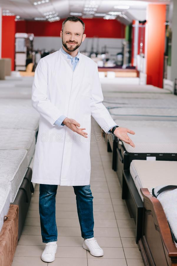 Smiling shop assistant pointing at orthopedic mattresses in white coat. In furniture shop royalty free stock photos