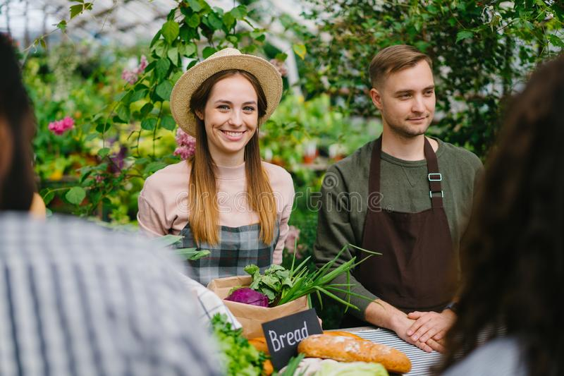 Smiling shop assistants selling organic food to customers in farm market stock image