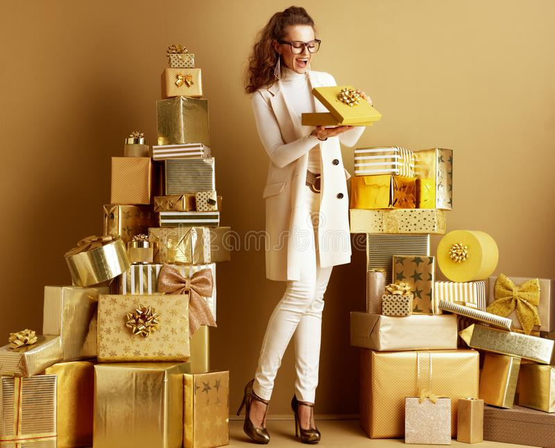 Smiling shopper woman opening golden present box with bow royalty free stock photo