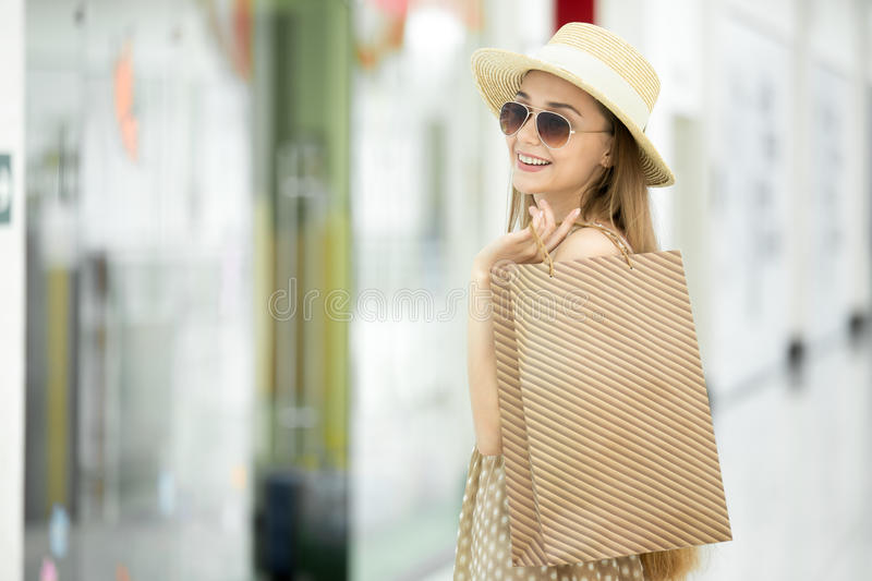 Smiling shopper woman in shopping centre. Side view portrait of young pretty smiling fashion woman wearing hat and sunglasses and holding shopping bag, looking stock photos