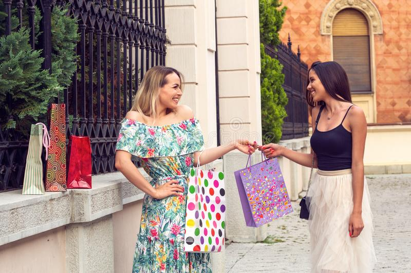 Shopping girls in the street with bags royalty free stock photos