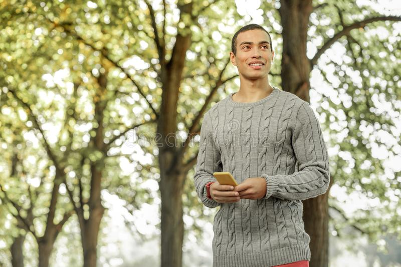 Smiling short-haired man in warm sweater looking for friend royalty free stock image