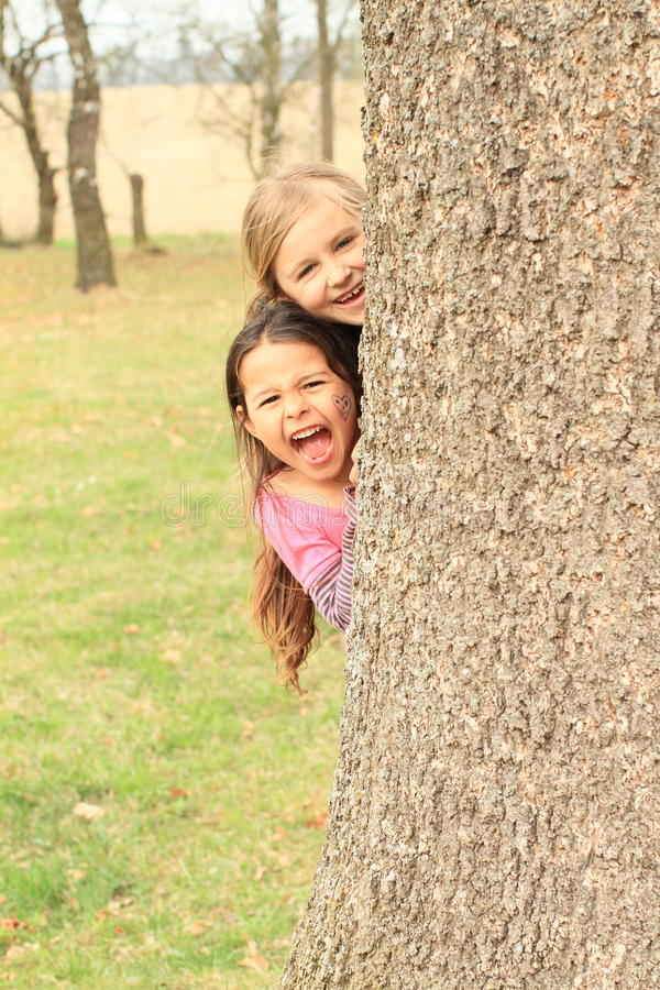 Smiling and shouting girls hiding behind tree. Cute little kids - smiling and shouting girls hiding behind trunk of a tree royalty free stock photography