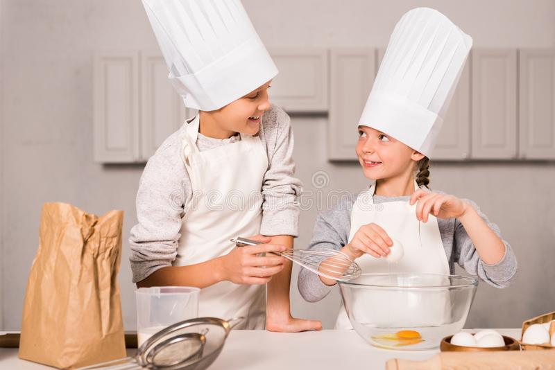 Smiling sister and brother in chef hats and aprons whisking eggs in bowl at table. In kitchen royalty free stock image