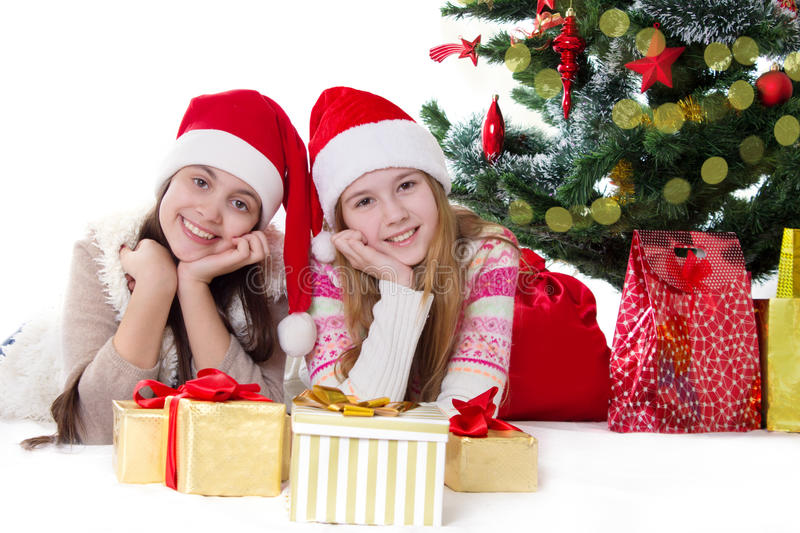 Smiling sisters in Santa hats lying under Christmas tree royalty free stock image