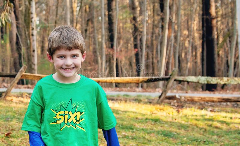 Smiling six year old boy playing outside royalty free stock photography