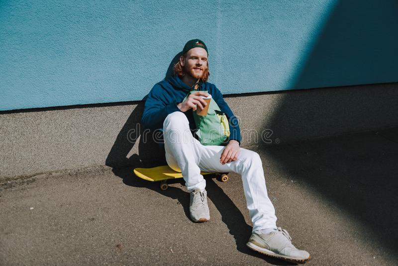 Smiling skater man is drinking coffee outdoor. Urban lifestyle and activity. Full length portrait of young smiling hipster guy sitting on his skateboard near stock photos