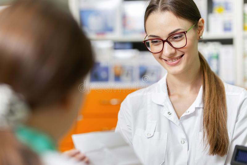 A smiling slim lady with dark hair and glasses,wearing a lab coat,is talking with a visitor and reads a prescription in royalty free stock photo