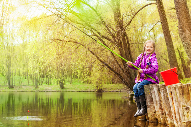 Smiling small girl fishing near beautiful pond. Holding fishrod with forest background royalty free stock photography