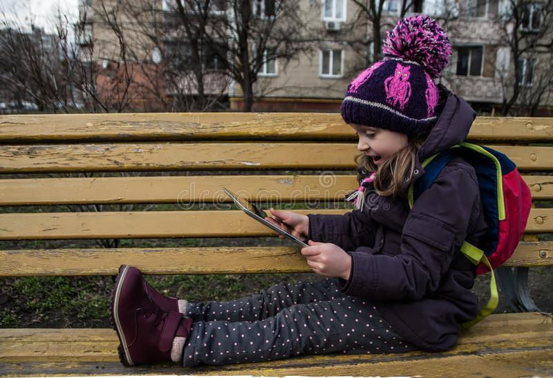 Smiling small girl sitting and holding computer in her hands, outdoors stock photography