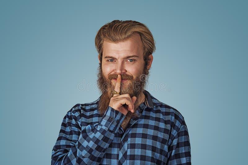 Smiling smug man hipster guy keeps a secret royalty free stock photography