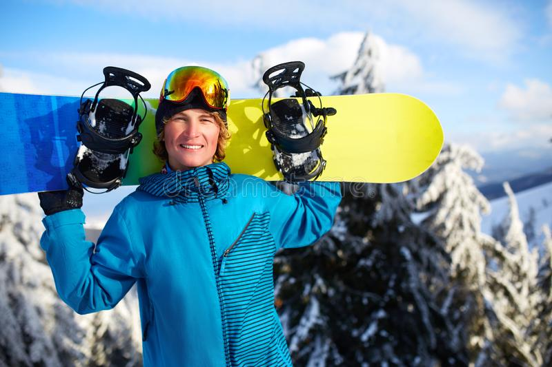 Smiling snowboarder posing carrying snowboard on shoulders at ski resort near forest before backcountry freeride and stock photos
