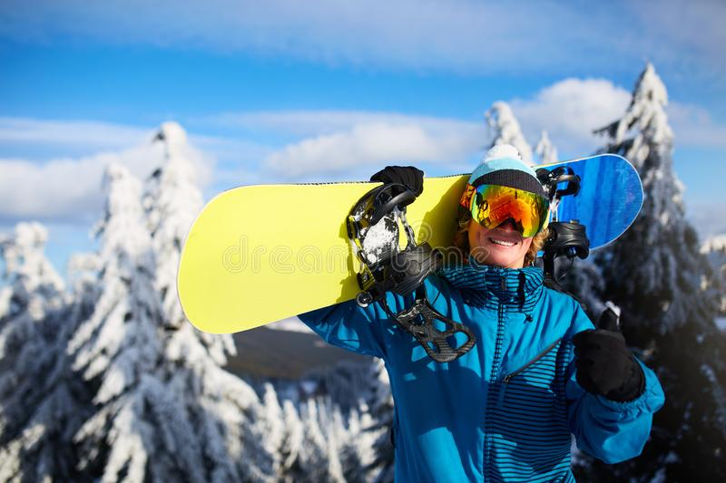 Smiling snowboarder posing carrying snowboard on shoulders at ski resort near forest before freeride session. Rider royalty free stock images