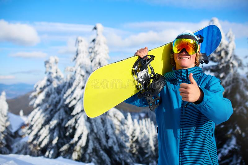 Smiling snowboarder posing carrying snowboard on shoulders at ski resort near forest before freeride session. Rider stock photography