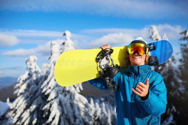 Smiling snowboarder posing carrying snowboard on shoulders at ski resort near forest before freeride session. Rider royalty free stock photos