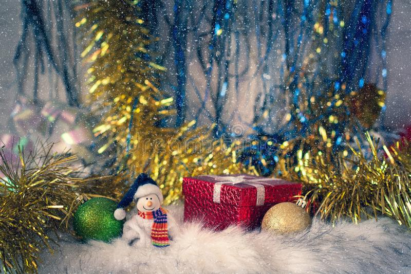 A smiling snowman in a scarf next to gifts and Christmas toys on the background of tinsel and snow. royalty free stock image