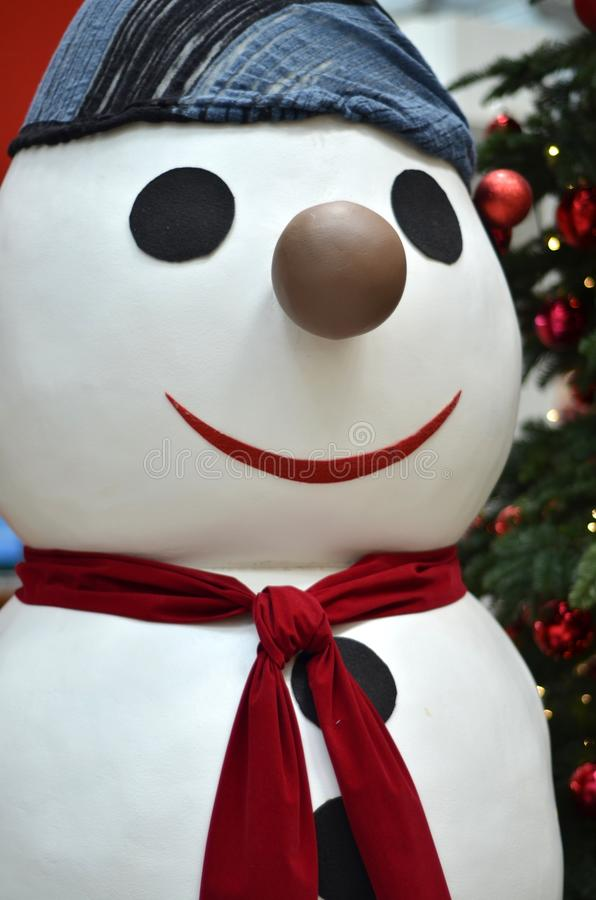 Smiling Snowman. A smiling snowman standing beside a Christmas tree stock photography