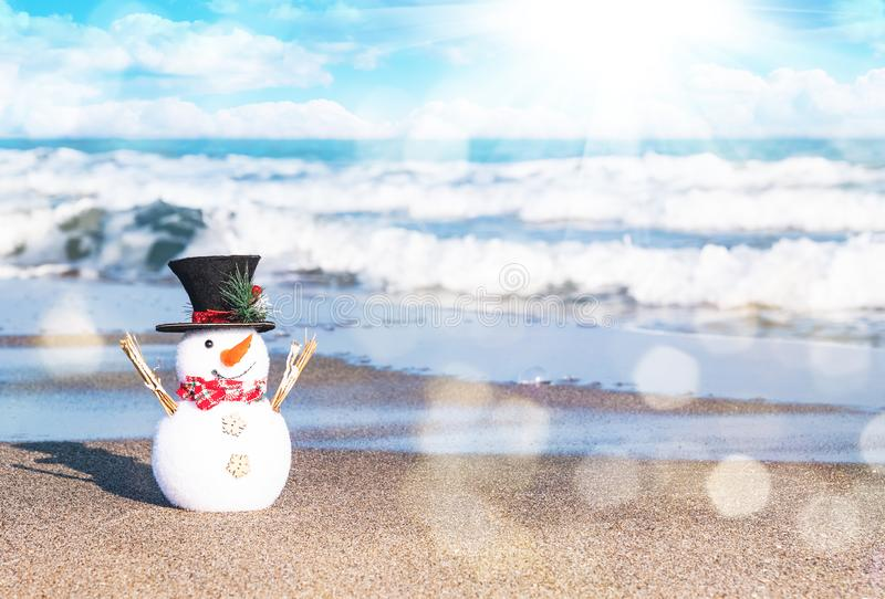 Smiling snowman at sunny beach. Holiday concept for Merry Christmas and Happy New Years cards stock photos