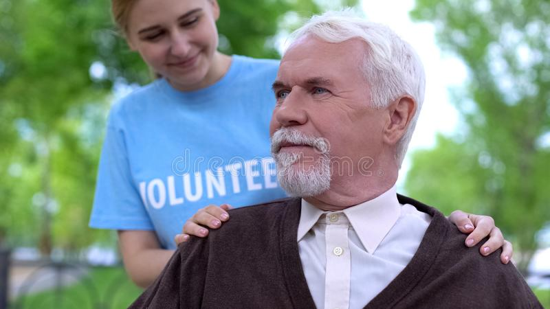 Smiling social worker taking care of aged pensioner, nursing home volunteering. Stock photo royalty free stock photo