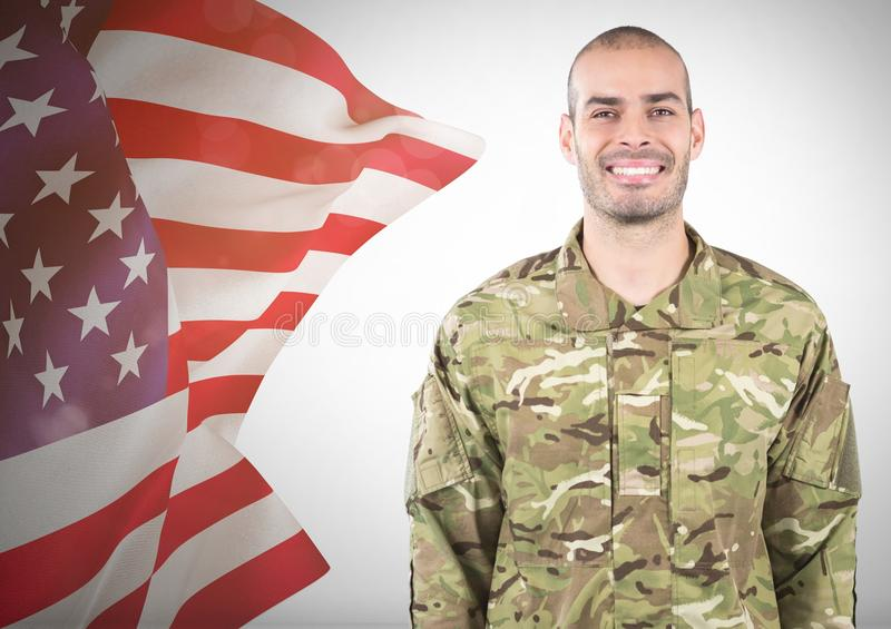 Smiling soldier near fluttering american flag. Digital composite of Smiling soldier near fluttering american flag royalty free stock photography
