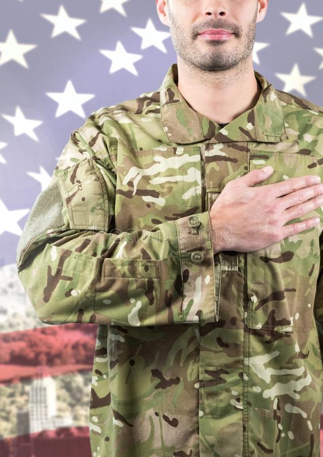 Smiling soldier putting his hand on his heart against american flag background stock photos