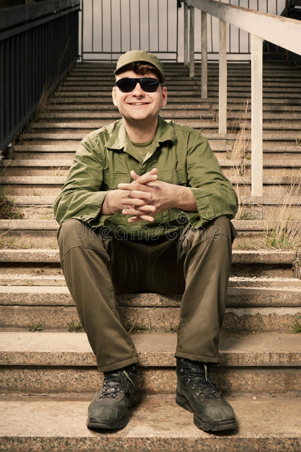 Smiling soldier in sunglasses on stairs stock photo