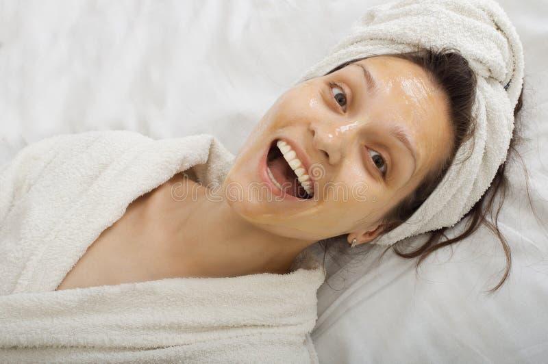 Smiling spa girl in a honey facialmask royalty free stock photo