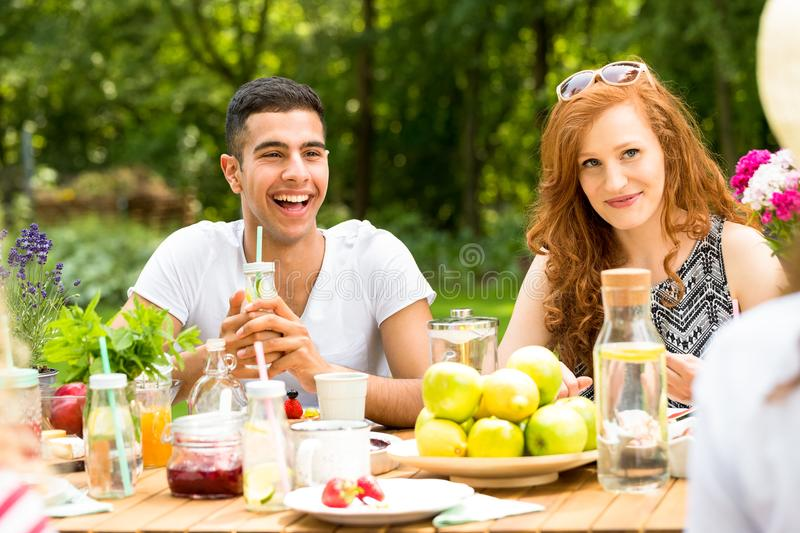 Smiling spanish man and happy woman drinking and eating during p. Smiling spanish men and happy women drinking and eating during party in the garden royalty free stock photos