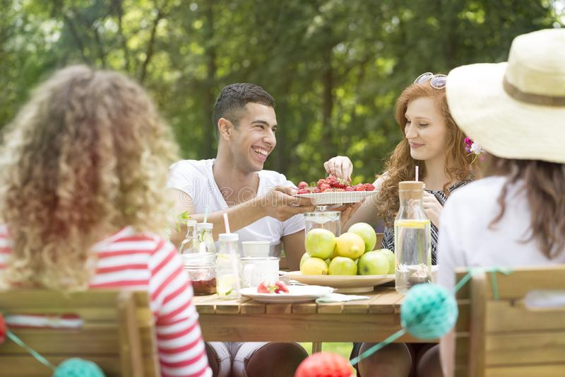 Smiling spanish man sharing food with happy woman during meeting stock photos