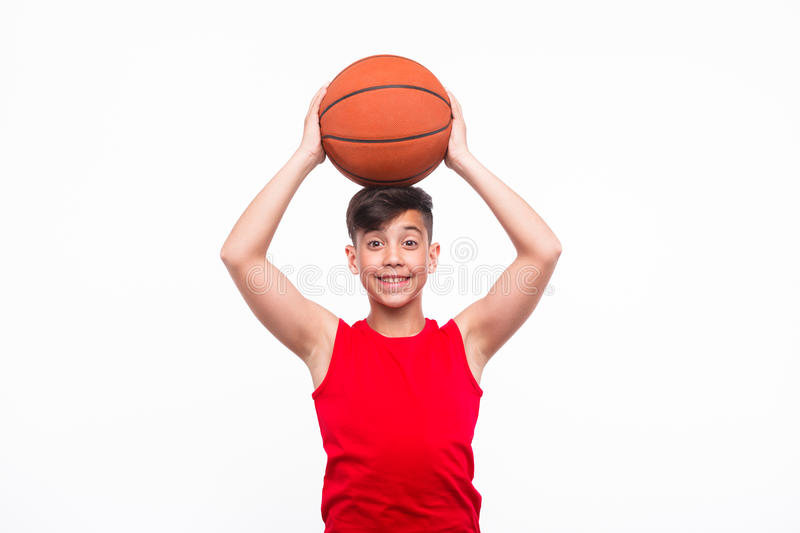 Smiling sportive kid with basketball. Content boy in sportswear holding basketball on head and smiling at camera on white stock image