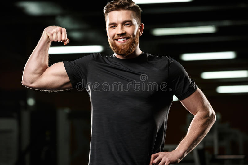 Smiling sports man showing his biceps. royalty free stock photos
