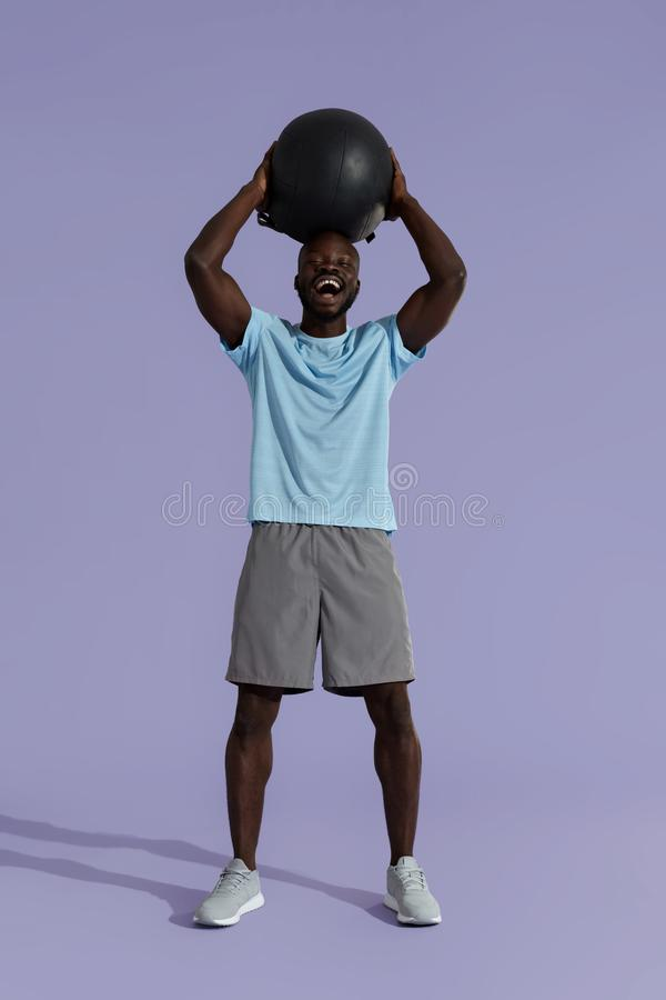 Smiling sports man in sports wear with med ball on background stock photo