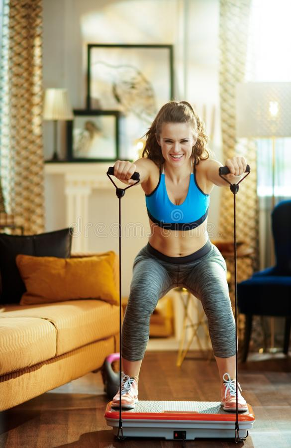 Smiling sports woman training using vibration power plate royalty free stock image
