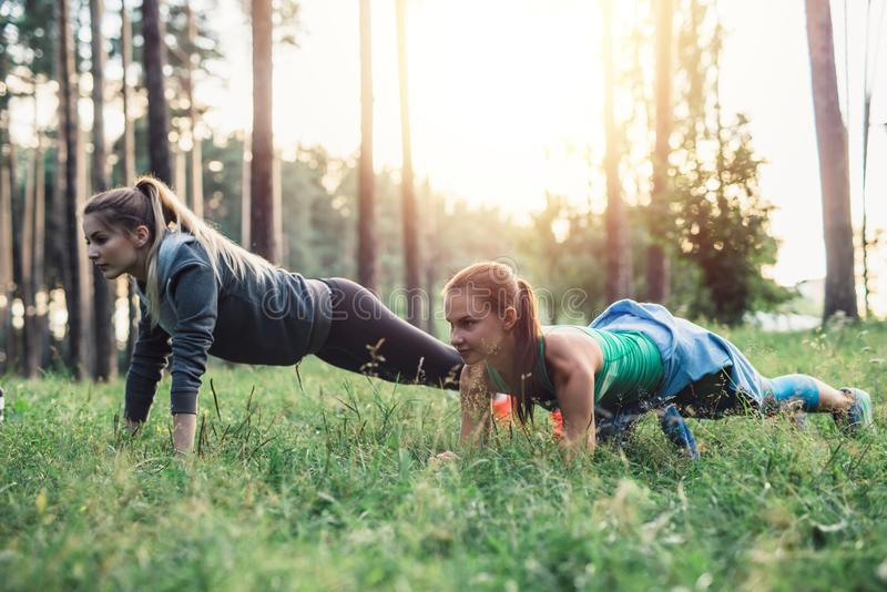 Smiling sportswomen having outdoor morning training standing in plank pose on grass in park stock photo